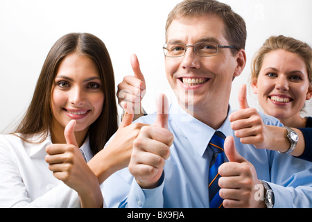 Team of three office worker's give the thumb's up sign - Stock Photo