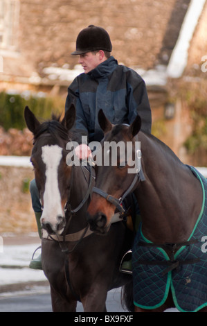 A local rider with two horses in the Cotswold village of Broadway in Worcestershire, England. - Stock Photo