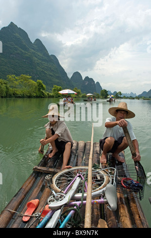 Chinese couple transporting tourists along the Yulong River on a bamboo raft, Yangshuo, Guangxi, China. - Stock Photo