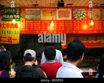a queue of Chinese citizens wait for fast food from a food stall in a backstreet of Beijing - Stock Photo