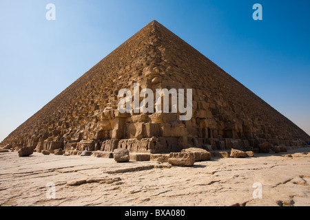 Policeman stands guard at the base of the Pyramid of Khufu (Cheops) showing relative scale of human to building - Stock Photo