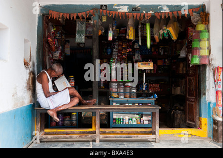 Indian man sitting reading outside a rural South Indian village shop - Stock Photo
