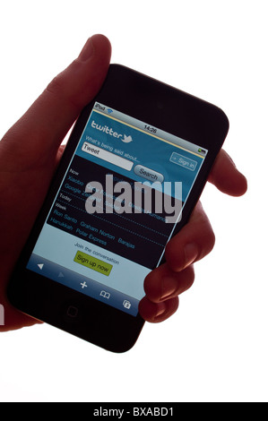 The new Apple Ipod touch 4th generation 4G media player with internet connection showing twitter website on a white - Stock Photo