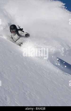 A snowboarder making a turn towards the camera in deep powder snow, with a cloud of powdery snow behind him. - Stock Photo
