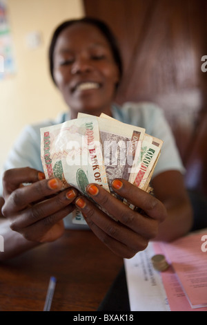 An accountant counts cash (Ugandan Shillings) in an office in Mbale, Eastern Uganda, East Africa. - Stock Photo