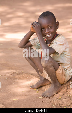 A young barefoot boy smiles in Bulowooza Village, Iganga District, Eastern Uganda, East Africa. - Stock Photo