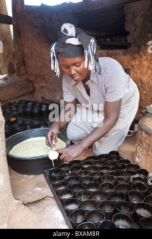 A baker (Rehama Mbabazi) pours batter into a cakepan in Mutukula Village, Iganga district, Eastern Uganda, East - Stock Photo