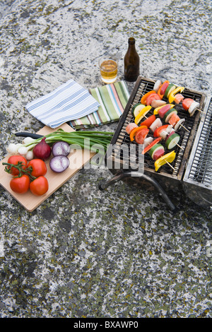 Barbecue grill with vegetables on rock - Stock Photo