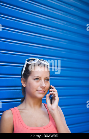 Young woman in front of blue wall, talking on phone - Stock Photo