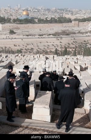 group of orthodox jews praying at a tomb at Mount of Olives cemetery with Old City in BKGD. Jerusalem. Israel - Stock Photo
