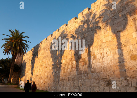 sunset on the Old City Walls promenade near Jaffa Gate with palm trees shadows and couple walking by. Jerusalem. - Stock Photo