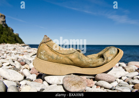 Old damaged shoe on stone beach - Stock Photo