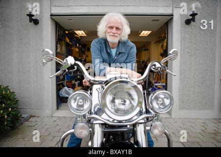 Portrait of senior man on vintage motorbike - Stock Photo
