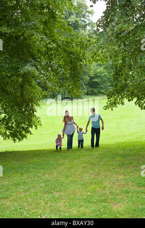 Parents walking with children in park - Stock Photo