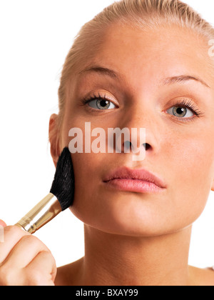 Young woman applying blusher, close-up - Stock Photo