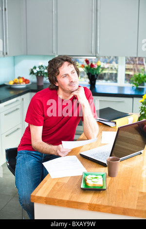 Mid adult man working from home - Stock Photo
