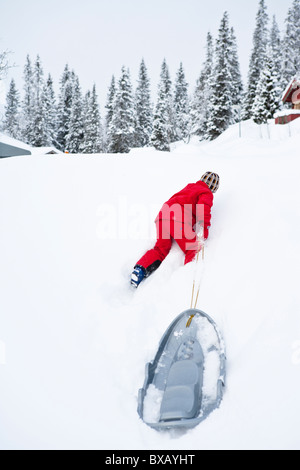 Child pulling sledge up hill in winter landscape - Stock Photo