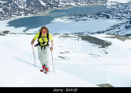 Man telemark skiing in mountain scenery - Stock Photo