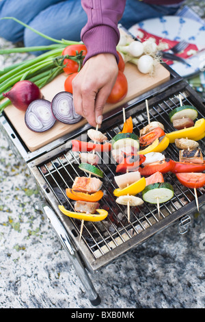 Person holding skewer with vegetables on grill - Stock Photo