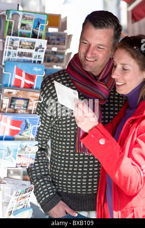Couple buying postcards from outdoor stall - Stock Photo
