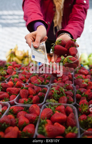 Close-up mid section of woman paying for basket of strawberries - Stock Photo