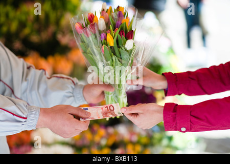 Person buying bunch of flowers from vendor - Stock Photo
