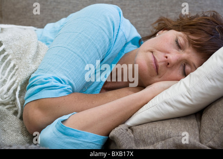 Mature woman lying on bed - Stock Photo