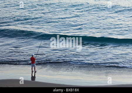 Lone man fishing on beach - Stock Photo