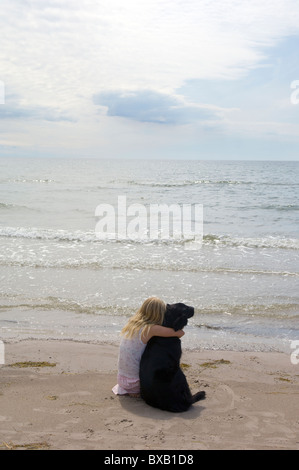 Girl with dog sitting on beach - Stock Photo