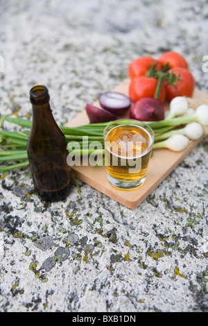 Vegetables and beer on chopping board - Stock Photo