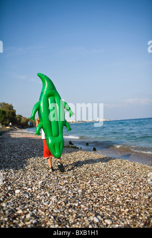 Boy walking on beach with inflatable - Stock Photo