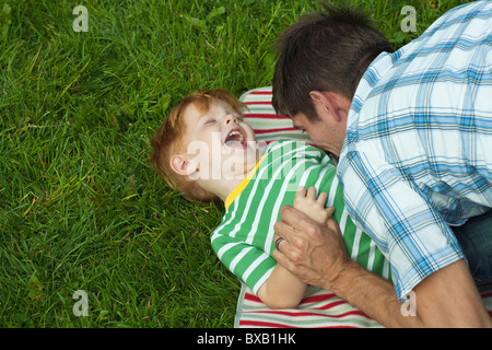 Mid adult father playing with son - Stock Photo