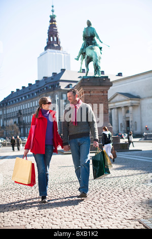 Couple with shopping bags, walking in city - Stock Photo