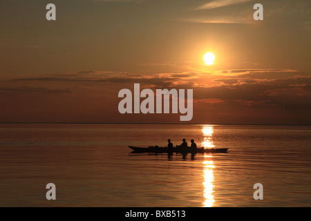 People in rowing boat during sunset - Stock Photo