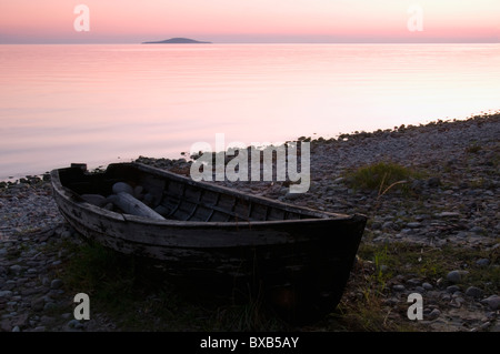 Row boat on shore at sunset - Stock Photo