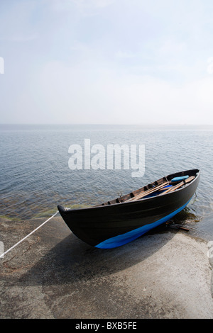 Small boat moored on coast - Stock Photo
