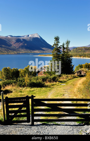 Small house on sea side, mountain in the background - Stock Photo