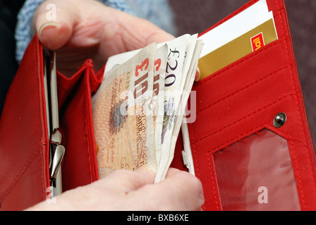 pensioner with open purse showing English currency notes - Stock Photo