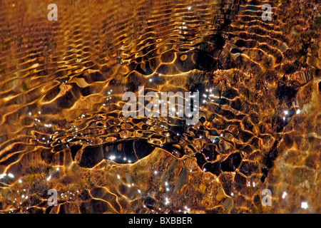 Close view of reflections of the water waves on the stream of a river. - Stock Photo