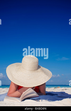 Woman in a large sun hat reading on a Caribbean beach