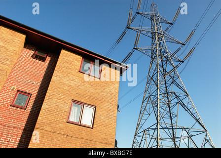 Pylon next to house East London UK - Stock Photo