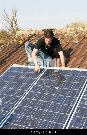 Fitting Photovoltaic panels onto the roof of a house North london UK - Stock Photo