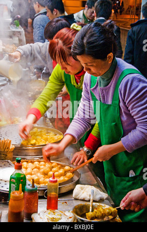 Asian women preparing food at outdoor food stall on city street in downtown Hong Kong China - Stock Photo