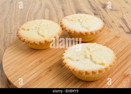 Festive sweet mince pies from low perspective arranged on wooden board. - Stock Photo
