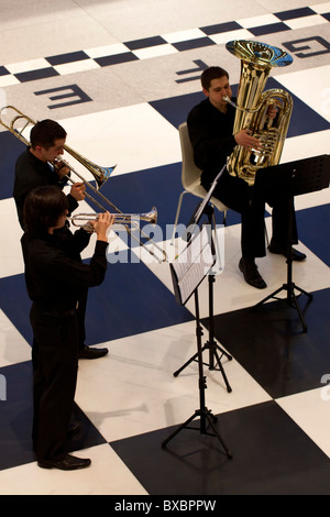 A brass band giving a concert on a large floor chessboard in Stary Browar, Poznan, Poland - Stock Photo