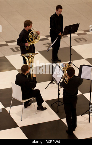 A brass quartet giving a concert on a large floor chessboard in Stary Browar, Poznan, Poland - Stock Photo