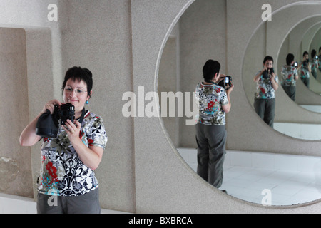 Woman with a camera in a hall of mirrors, Jameos del Agua, designed by César Manrique, Lanzarote, Canary Islands, - Stock Photo