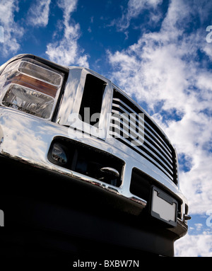 Close-up of the front of a shiny Truck. Lots of chrome. Low angle looking up towards blue sky with partial clouds. - Stock Photo