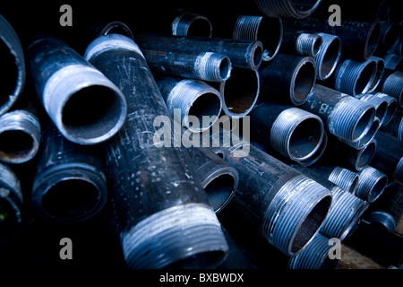 Closeup with wide angle on a group of pipes stacked with open end facing camera. - Stock Photo