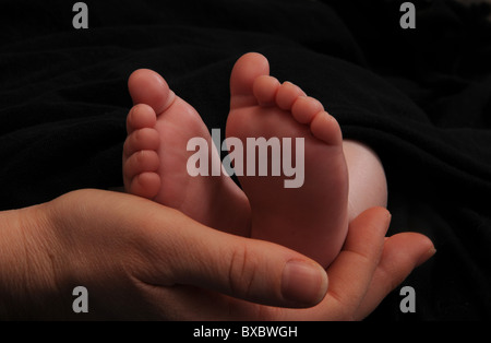 The feet of a 4-month-old child are cradled in the hands of their mother. - Stock Photo